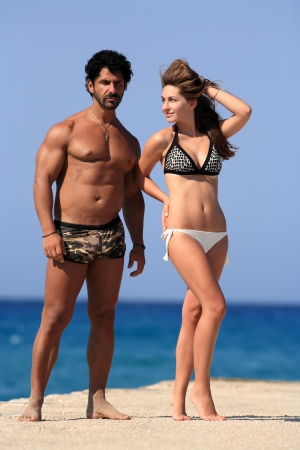 young happy couple posing at the beach photo