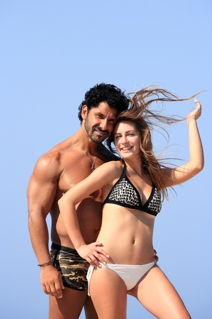 young happy couple posing at the beach