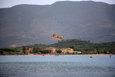 ZAKYNTHOS, GREECE- AUG 1  Canadair CL-415 or Bombardier 415 approaching the sea to take water during big fire at the mountain close to the village Alykes, August 01, 2012 Zakynthos, Greece Stock Photo - 14939165