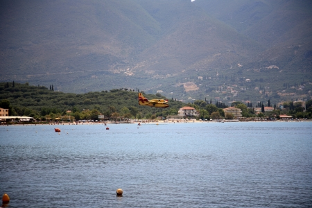 ZAKYNTHOS, GREECE- AUG 1  Canadair CL-415 or Bombardier 415 approaching the sea to take water during big fire at the mountain close to the village Alykes, August 01, 2012 Zakynthos, Greece Stock Photo - 14939167