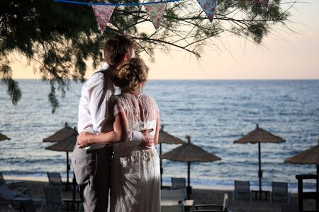 bride and groom hug each other and looking at the sea photo
