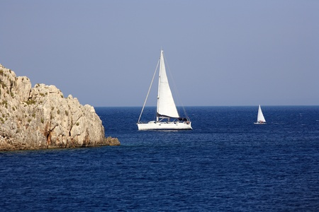 big and small sailing boats in the blue water of a greek island photo