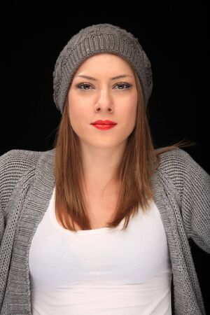 pretty girl with knit grey cap on a black background Stock Photo - 15608619