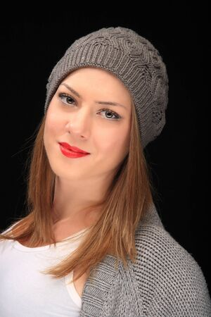 pretty girl with knit grey cap on a black background Stock Photo - 15608622