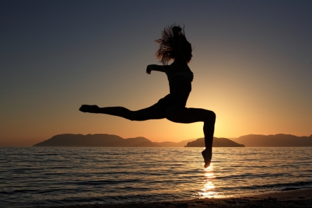 sunset and silhouette of a beautiful dancer in the beach Stock Photo