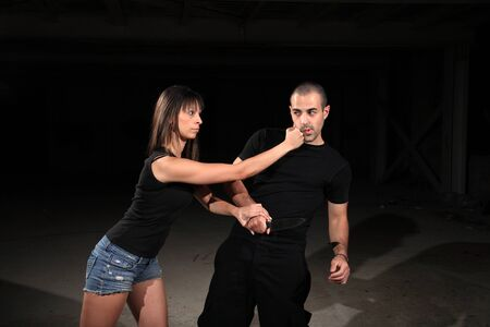 defenses: martial arts female instructor exercising with young man