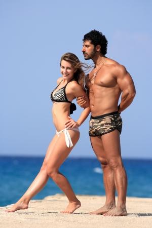 bikini couple: young happy couple posing at the beach