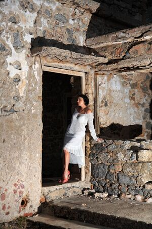 sexy girl with white dress posing outside an old building photo