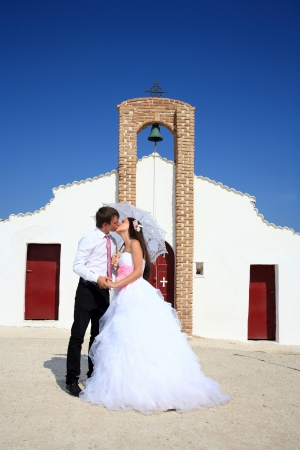portrait of a beautiful bride and groom with a church on the background