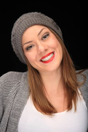 pretty girl with knit top and grey cap on a black background photo