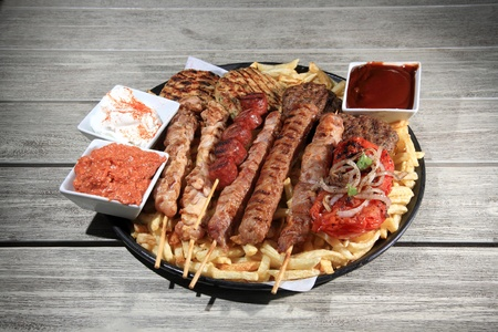 mix grill served on a plate with fried potatoes and variety of sauces