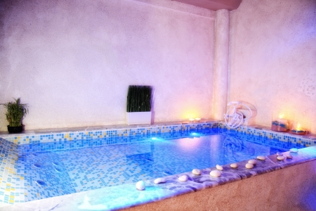 hydromassage: hydro-massage indoor  pool decorated with small stones and candles