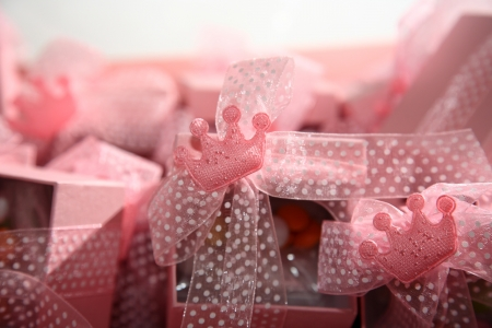 small pink crowns decorate a box christening favors