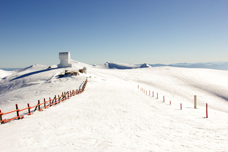small observatory on the top of a mountain with snow Stock Photo