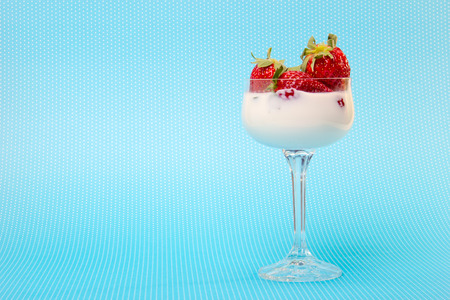 fresh strawberries on a glass filled with cream  photo