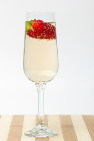 fresh strawberry on a glass filled sparkling wine photo