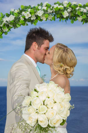 flower bouquet: bride and groom kissing while holding a white rose flower bouquet