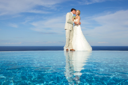 portrait of a bride and groom kissing on a infinity pool against the sky