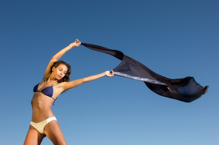 scarf beach: Beautiful young girl with scarf dancing at the beach against the blue sky