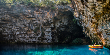 kefallonia: small boat inside a cave lake with blue water in kefallonia greece