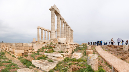 SOUNIO, GREECE - MARCH 27, 2016: Tourists visting and admire the ruins of an ancient Greek temple of Poseidon under dramatic cloudy sky, Cape Sounion, Greece