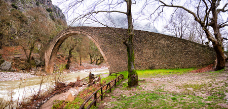 Arched stone bridge of Pyli in a rainy day,Thessaly, Greece