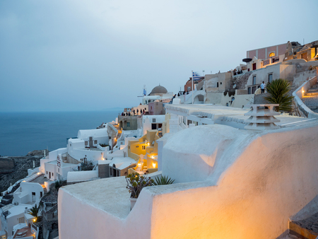 Small white houses with lights late in the afternoon in Oia, Santorini island,Greece
