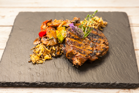 Grilled steak served with rice and vegetables on a graphite plate