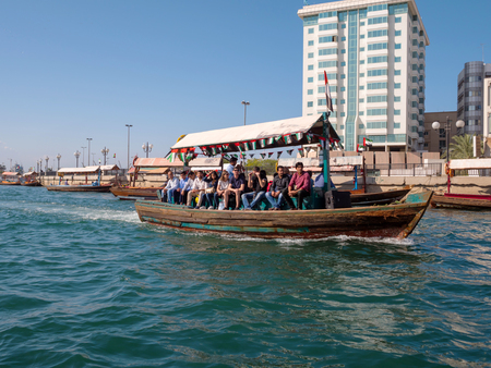 DUBAI,UAE - DECEMBER 19, 2017: Abra ferries with tourists crossing the Dubai Creek that connects Deira and Bur Dubai Editorial