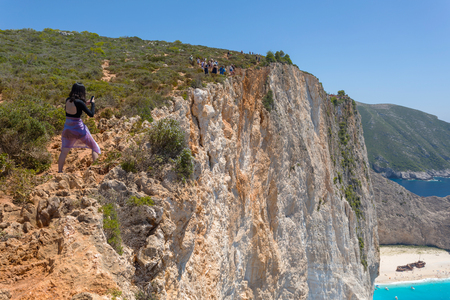 ZAKYNTHOS, GREECE - JULY 21, 2018: Tourists at the edge of the cliff to take photos of the famous beach with an old shipwreck in the island of Zakynthos in Greece