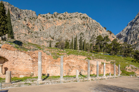 Ruins of Delphi archaeological site with snow in a winter day with sun