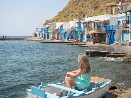 Girl on a small boat in Klima village in Milos island, Greece