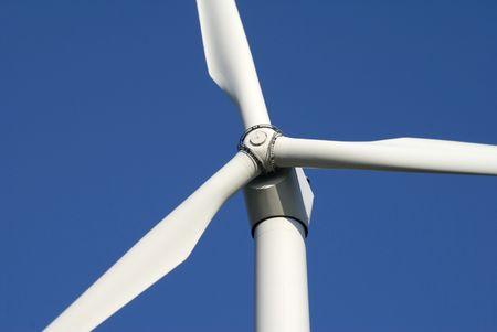 Close-up of wind turbine against blue sky photo