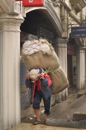 slave labor: DARJEELING INDIA - APRIL 2012   Man carrying big sack on street, morning view of Darjeeling, India as of April 12, 2012