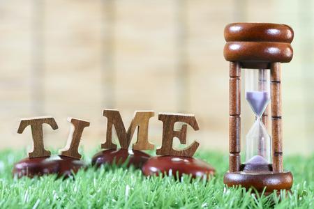 gestion del tiempo: Reloj de arena e alfabeto de madera, el concepto de gesti�n y en la idea de tiempo Foto de archivo
