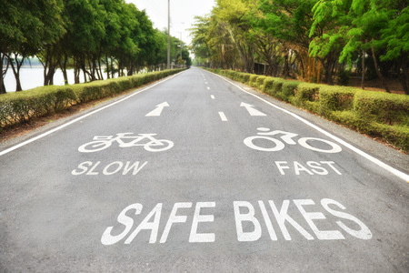 lanes: Safety concept, Safe bikes, slow and fast words with white arrow sign marking on road surface in the park for giving directions and separate lanes