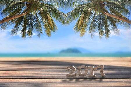 Wood number 2017 on plank on tropical beach background, happy new year concept and happy summer holiday idea Standard-Bild