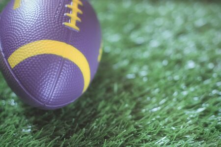 Healthiness concept and sport background idea, Close up of moving mini american football on the green grass Stock Photo