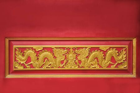 Golden dragon on red door background in Chinese temple Stock Photo