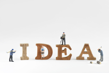 Miniature worker with wooden word of idea on white background, business success concept