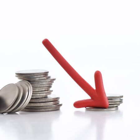 Arrow downwards with coins on white background, business recession concept and crisis idea Stock Photo