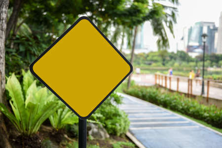 Blank yellow traffic sign at park background, copy space isolated