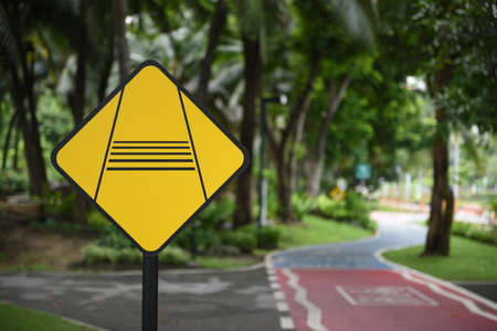 Precaución para disminuir la señal de tráfico del ciclista y carriles para bicicletas en Benchakitti Park