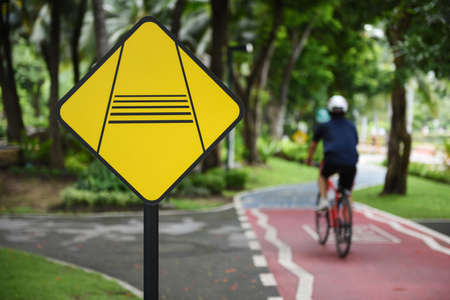BANGKOK, THAILAND - JULY 2017: Caution slow down rider traffic sign and rider on bike lanes at Benchakitti Park on JULY 10, 2017 in BANGKOK, THAILAND Stock Photo