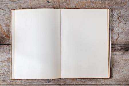 木製の背景上の古いオープン本のフラット レイアウト