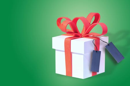 White gift box and red ribbon with blank card on green background