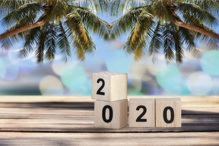 Wood cube number 2020 on planks on tropical beach background, happy new year concept and happy summer holiday idea