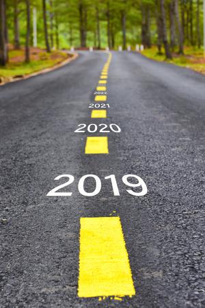 Número de 2019 a 2023 en la superficie de la carretera de asfalto con líneas de marcado, concepto de feliz año nuevo Foto de archivo