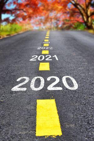 2020 bis 2023 auf Asphaltstraßenoberfläche mit Herbstsaisonhintergrund, Konzept des guten Rutsch ins Neue Jahr