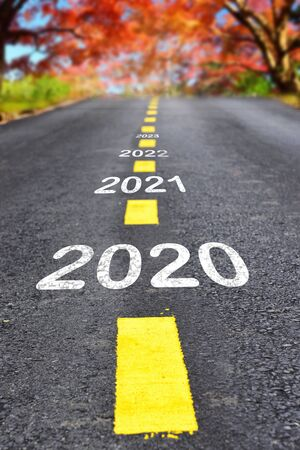 2020 to 2023 on asphalt road surface with autumn season background, happy new year concept